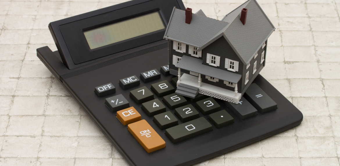 Cost of housing, A gray house and calculator on stone background