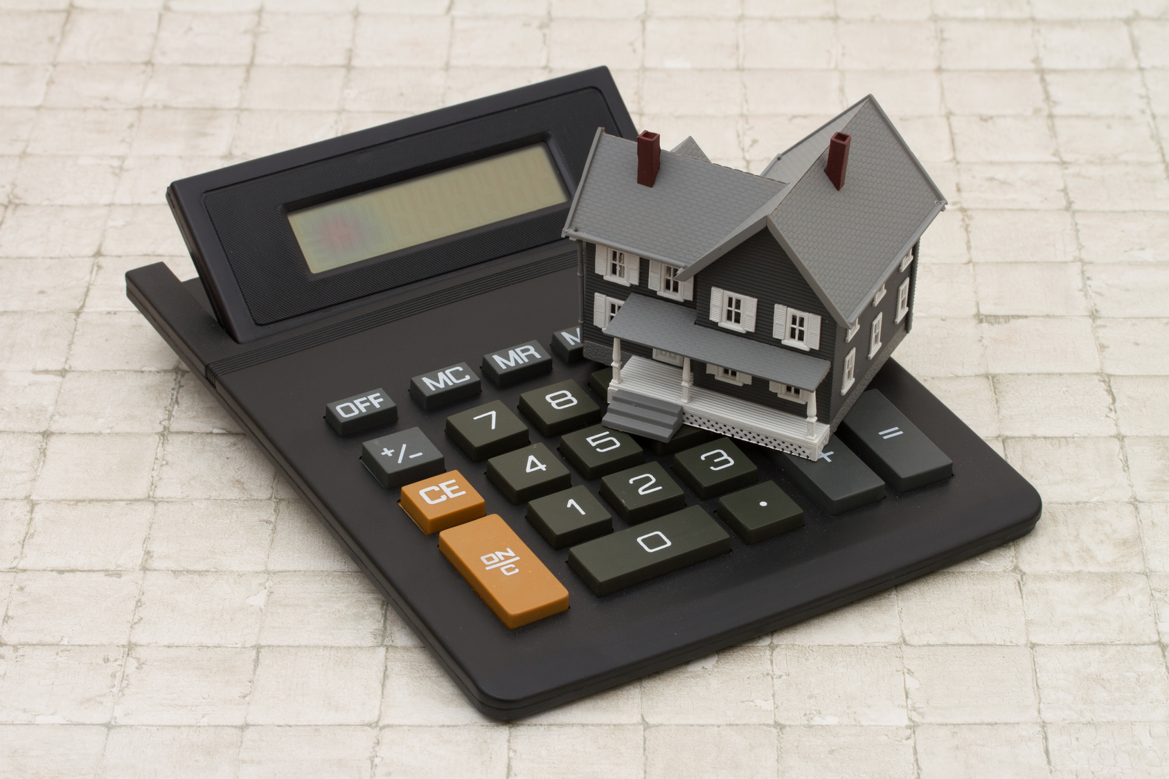 A gray house and calculator on stone background
