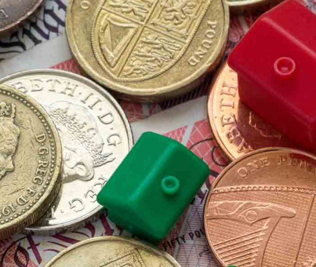 Imitation model red and green plastic houses with chimneys rest on top of British coins and notes of differing values and colors